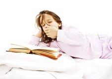 Enseñe a la muchacha que lee un libro en su cama Foto de archivo
