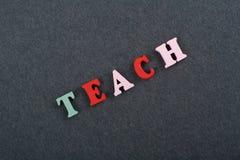 ENSEÑE a la palabra en el fondo negro del tablero compuesto de letras de madera del ABC del bloque colorido del alfabeto, copie e Imágenes de archivo libres de regalías