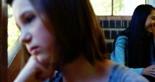 Enseñe a los amigos que tiranizan a una muchacha triste en pasillo de la escuela almacen de metraje de vídeo