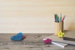 Enseñe los cuadernos, los lápices y otros artículos en fondo de madera imagen de archivo