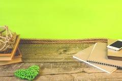 Enseñe los cuadernos, los lápices y otros artículos en fondo verde fotografía de archivo libre de regalías