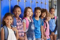 Enseñe a los niños delante de los armarios en vestíbulo de la escuela primaria foto de archivo libre de regalías