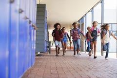 Enseñe a los niños que corren a la cámara en vestíbulo de la escuela primaria Fotografía de archivo libre de regalías