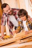 Enseñando a su hijo todo sobre la carpintería Foto de archivo