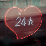 Enseigne au néon dans le coeur-étalage 24 heures, autour de l'horloge Image libre de droits
