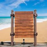 Enseigne en bois sur le fond de plage de tache floue Photographie stock