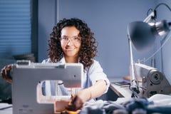 On enseigne la femme à coudre dans le studio de couture Photographie stock libre de droits