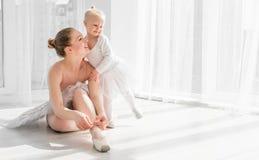 On enseigne peu de fille comment attacher des chaussures de pointe de ballet photos libres de droits