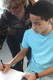 Enseignement vérifiant le travail de l'élève Images libres de droits