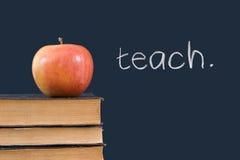 Enseignez écrit sur le tableau noir avec la pomme et les livres Images stock