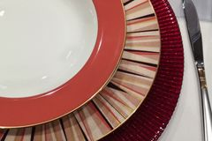 Ensemble élégant vide de table de texture différente de trois plats et couleur dans les ombres rouges servant sur une table photo stock