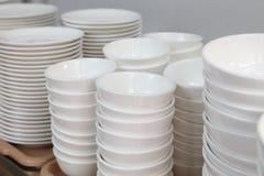 Ensemble blanc de plat en céramique, de plat, de tasse empilant vers le haut du support pour la cuisine et de conception de organ photo libre de droits
