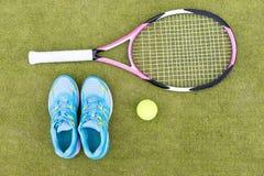 Ensemble d'équipement de tennis de raquette de tennis, de boule et d'espadrilles femelles Image libre de droits