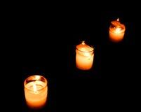 Ensemble d'allumer des bougies dans une rangée sur le fond foncé Photos libres de droits