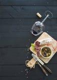 Ensemble d'apéritif de vin Verre de vin rouge, de saucisse française et d'olives sur le contexte en bois noir photo libre de droits
