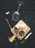 Ensemble d'apéritif de vin Verre de vin rouge, de saucisse française et d'olives sur le contexte en bois noir, vue supérieure Photographie stock