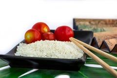 Ensemble d'Oriental de riz, de tomates, de baguettes, de feuille verte et de transport Image stock