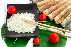 Ensemble d'Oriental de riz, de tomates, de baguettes, de feuille verte et de transport Photos stock