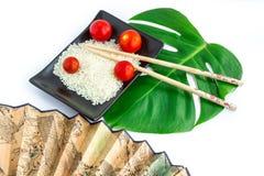 Ensemble d'Oriental de riz, de tomates, de baguettes, de feuille verte et de transport Images stock