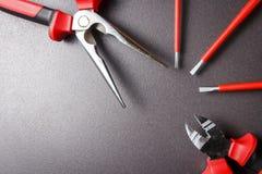Ensemble d'outils d'électricien sur le fond noir Le coupeur d'ornithorynque, de tournevis et de fil sont garnis de la fan Images libres de droits
