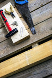Ensemble d'outils de bricolage : scie à métaux, pinces, vis, marteau, clous - sur une barre et conseils unplaned en bois Outils d Photographie stock libre de droits