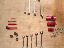 Ensemble d'outils pour la voiture réparant sur le fond en bois avec les voitures rouges de jouet de contraste Vue supérieure Image stock