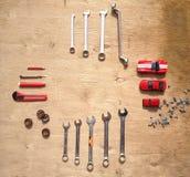 Ensemble d'outils pour la voiture réparant sur le fond en bois avec les voitures rouges de jouet de contraste Vue supérieure Photos libres de droits