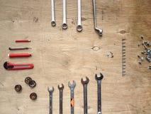Ensemble d'outils pour la voiture réparant sur le fond en bois avec les voitures rouges de jouet de contraste Vue supérieure Photographie stock libre de droits
