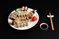 Ensemble d'unagi et de petits pains de sushi au fond noir Image stock
