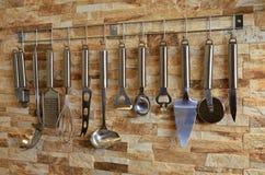 Ensemble d'ustensiles de cuisine accrochant sur le mur Photographie stock