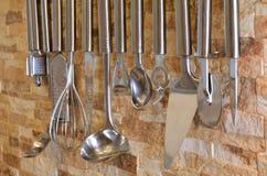 Ensemble d'ustensiles de cuisine accrochant sur le mur Image libre de droits