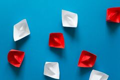 Ensemble de bateaux rouges et blancs d'origami sur le fond de papier bleu Concept de déplacement d'été Image stock