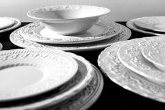 Ensemble de beaux plats en céramique blancs de soulagement de dîner sur le fond noir Images libres de droits