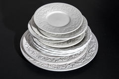 Ensemble de beaux plats en céramique blancs de soulagement de dîner sur le fond noir Images stock