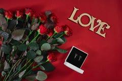 Ensemble de bijoux de boucles d'oreille d'or dans un boîte-cadeau et des roses rouges sur le fond rouge Photographie stock libre de droits