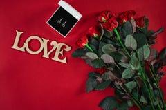 Ensemble de bijoux de boucles d'oreille d'or dans un boîte-cadeau et des roses rouges sur le Re Photos stock