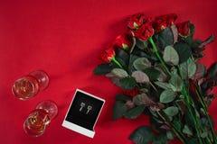 Ensemble de bijoux de boucles d'oreille d'or dans un boîte-cadeau et des roses rouges sur le Re Photographie stock