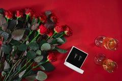 Ensemble de bijoux de boucles d'oreille d'or dans un boîte-cadeau et des roses rouges sur le Re Photo libre de droits