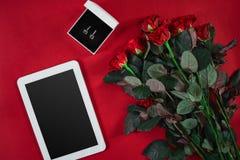 Ensemble de bijoux de boucles d'oreille d'or dans un boîte-cadeau et des roses rouges sur le Re Photo stock