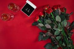 Ensemble de bijoux de boucles d'oreille d'or dans un boîte-cadeau et des roses rouges sur le Re Photos libres de droits