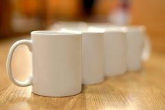 Ensemble de blanc de tasses dans la rangée diagonale au-dessus d'une table en bois Photos stock