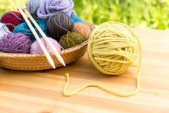 Ensemble de boules et d'aiguilles colorées de fil sur la fin de plat de paille  Images libres de droits