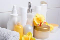 Ensemble de bouteilles cosmétiques blanches avec des orchidées au-dessus de mur carrelé photographie stock libre de droits