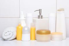 Ensemble de bouteilles cosmétiques blanches et oranges au-dessus de mur carrelé Images stock