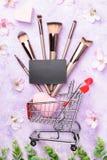 Ensemble de brosses de maquillage sur le fond rose Photos stock