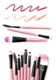 Ensemble de brosses roses de maquillage avec la trace de rouge à lèvres d'isolement sur le fond blanc photos stock
