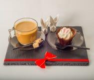 Ensemble de café noir dans une tasse, deux petits pains avec une boisson jaune dedans Images libres de droits