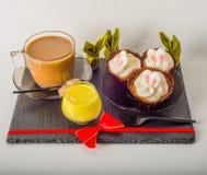 Ensemble de café noir dans une tasse, deux petits pains avec une boisson jaune dedans Photo stock