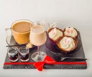 Ensemble de café noir dans une tasse, deux petits pains avec une boisson jaune dedans Photo libre de droits