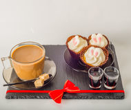 Ensemble de café noir dans une tasse, deux petits pains avec une boisson jaune dedans Photos libres de droits